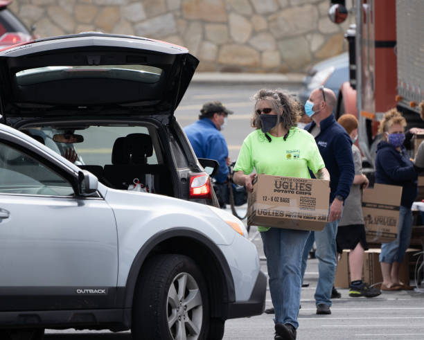 Potato Giveaway Berks County, Pennsylvania -May 20, 2020- Volunteer puts box of potatos in car.  Dieffenbach's Potato Chips gave away 40,000 pounds of potatoes today at the Berkshire Mall. curbsidepickup stock pictures, royalty-free photos & images