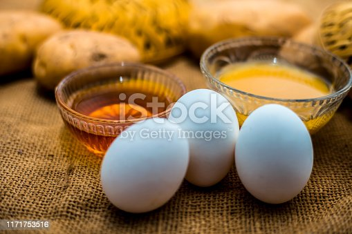 istock Potato juice plus honey plus egg yolk face mask for dry and damaged hair on the wooden surface along with raw potato, egg and honey present on the surface. 1171753516
