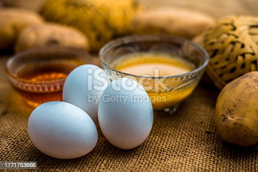 istock Potato juice plus honey plus egg yolk face mask for dry and damaged hair on the wooden surface along with raw potato, egg and honey present on the surface. 1171753666