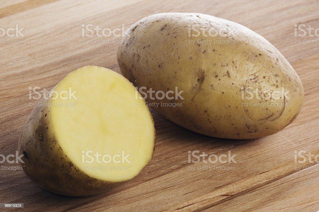 Potato on a wooden kitchen board royalty-free stock photo