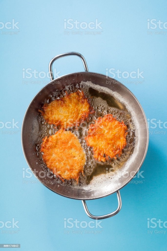 potato pancakes latkes are cooked in oil on a metal frying pan on a blue background stock photo