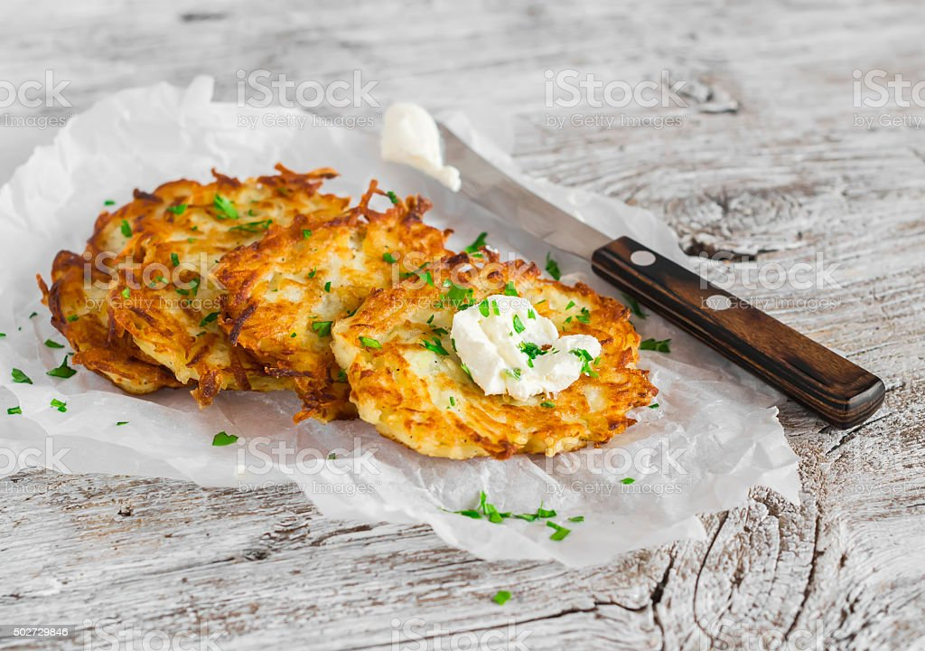 Potato pancakes or latkes on a light rustic wood surface stock photo
