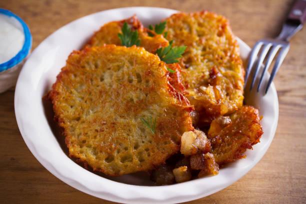 Panqueques de patata con vientre de cerdo frito y cebolla en tazón - foto de stock