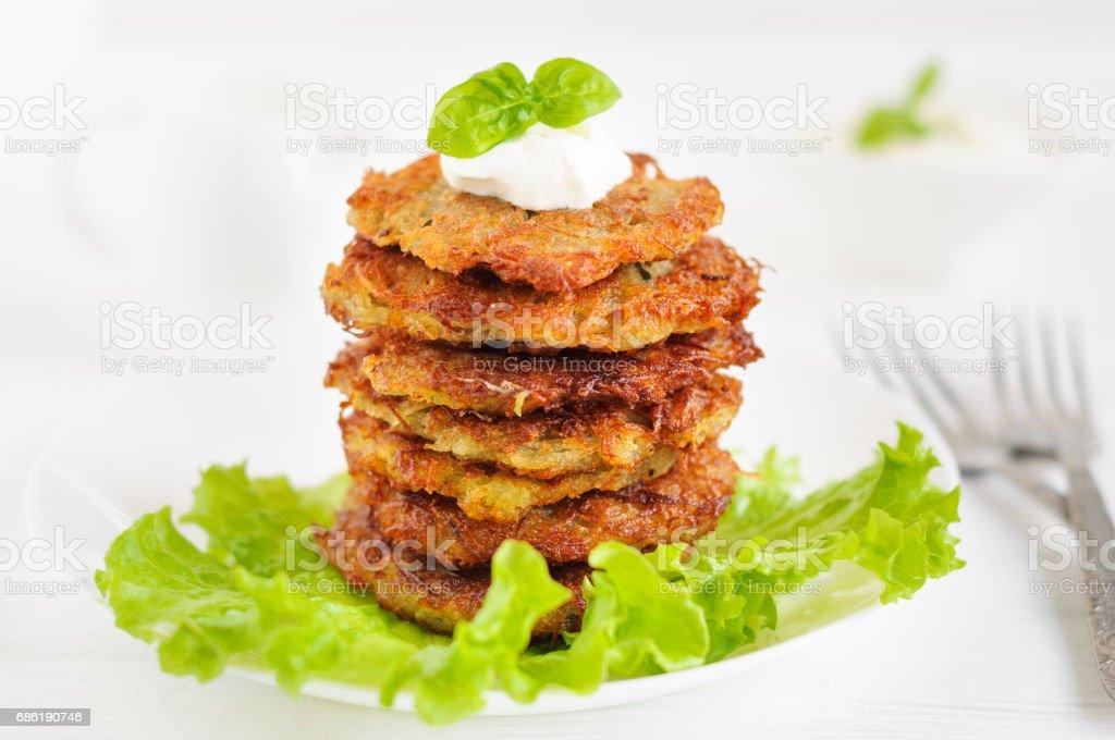 Potato pancakes with sour cream and lettuce stock photo