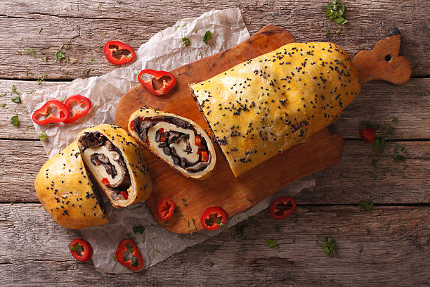 potato roll with forest mushrooms and pepper. horizontal top view - kartoffelroulade stock-fotos und bilder