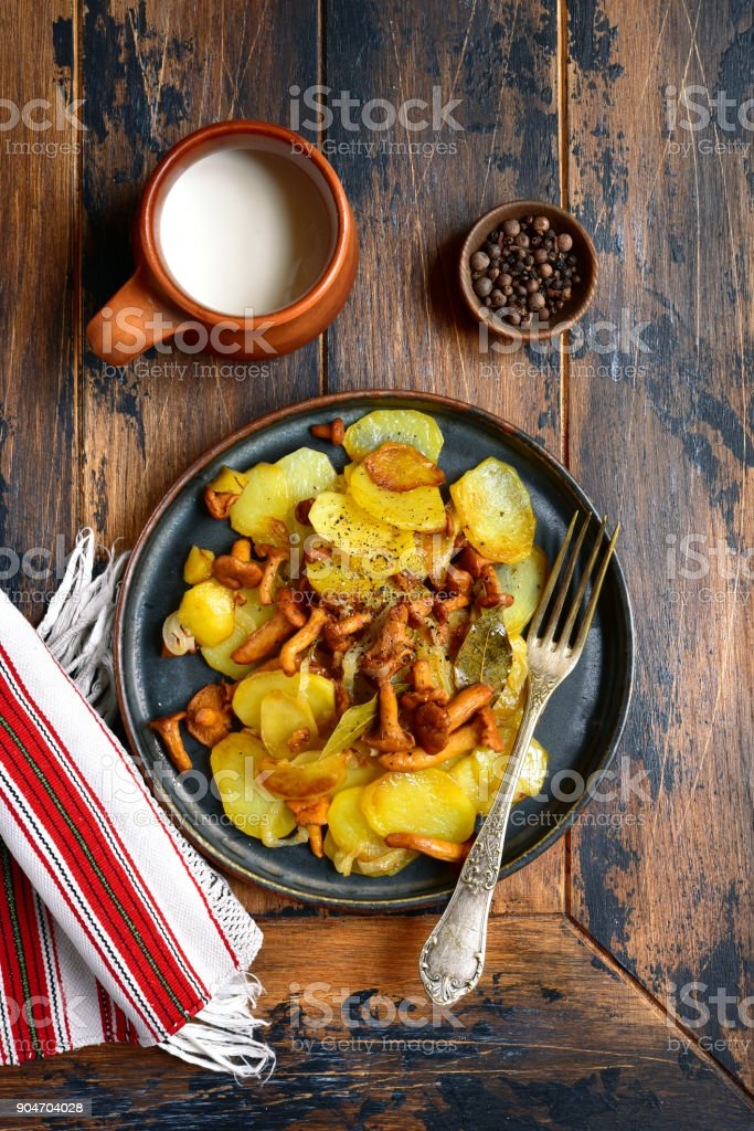 Potato slices fried with chanterelle mushrooms and onion stock photo