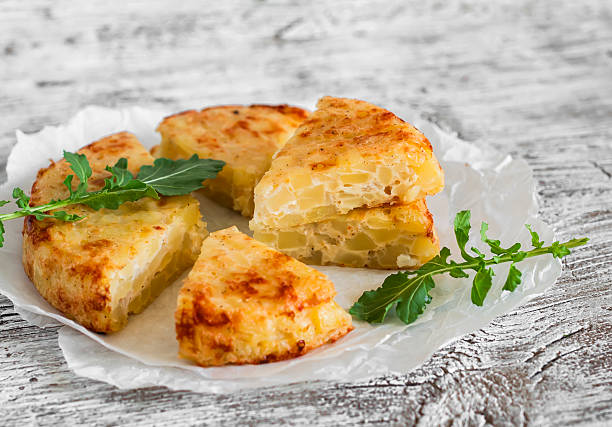 potato tortilla on a light wooden background - tortilla stock photos and pictures