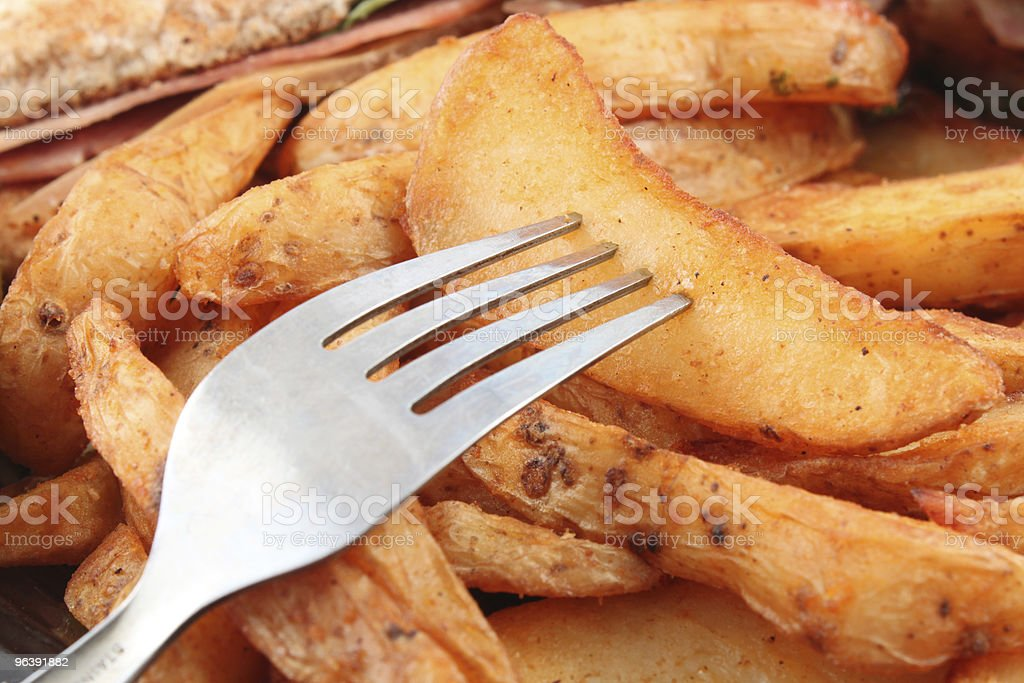 Potato wedges and fork royalty-free stock photo