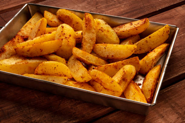 Potato wedges, oven baked, in a baking tray on a rustic background stock photo
