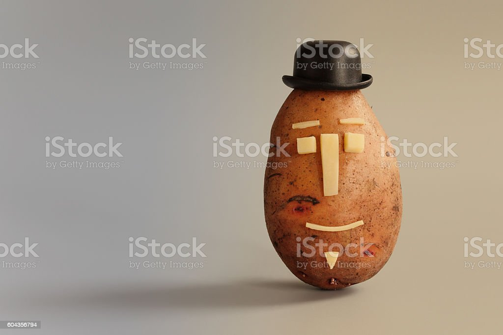Potato with funny face and black hat, copy space stock photo