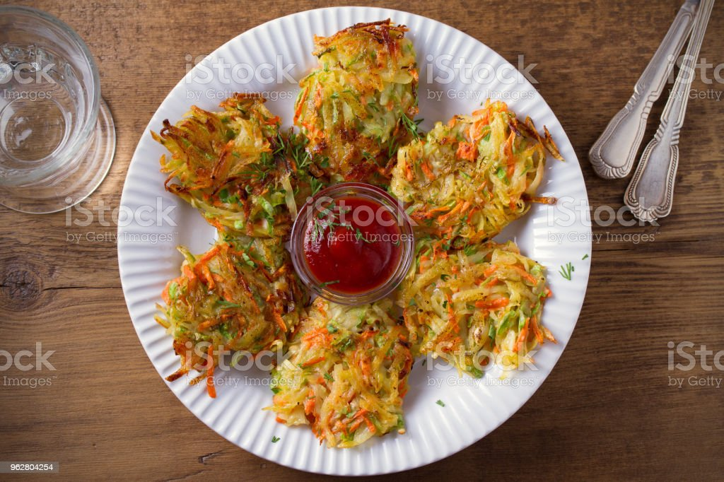 Potato Zucchini and Carrot Cakes. Vegetable fritters, latkes, draniki. Vegetable pancakes on white plate on wooden table - Foto stock royalty-free di Carota