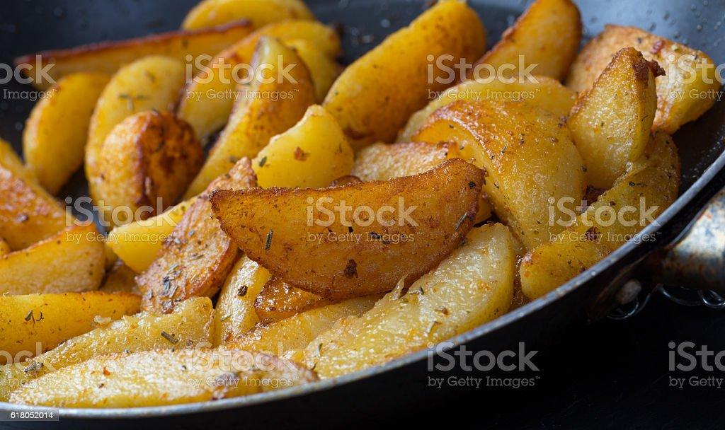 potatoe wedges in a pan stock photo