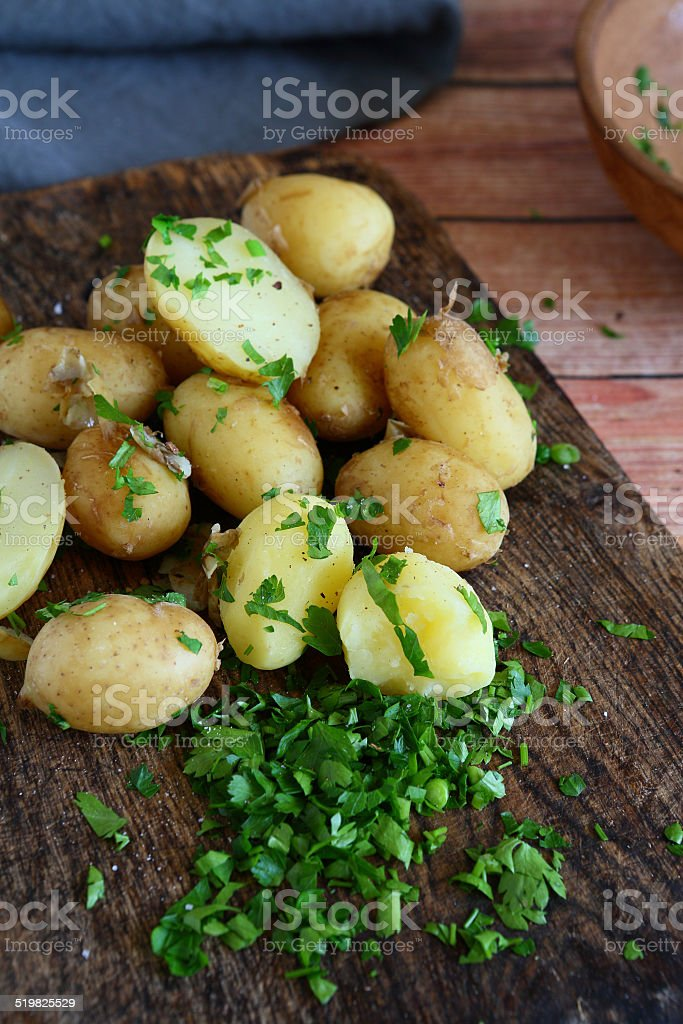 potatoes and greens on board stock photo