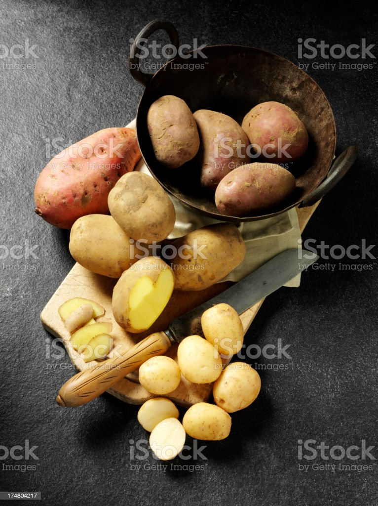 Potatoes and one Sweet Potato on a Slate Background royalty-free stock photo