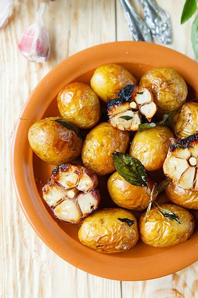 kartoffeln, die in ihrer haut mit knoblauch - knoblauchkartoffeln stock-fotos und bilder