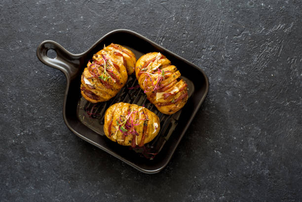 Potatoes baked with bacon, cheese and olive oil served on black plate stock photo