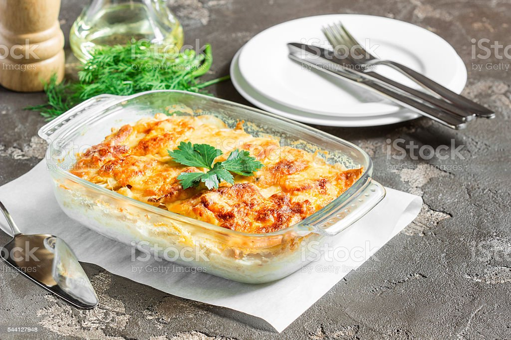 Potatoes baked with cheese, apples and fresh green vegetables stock photo