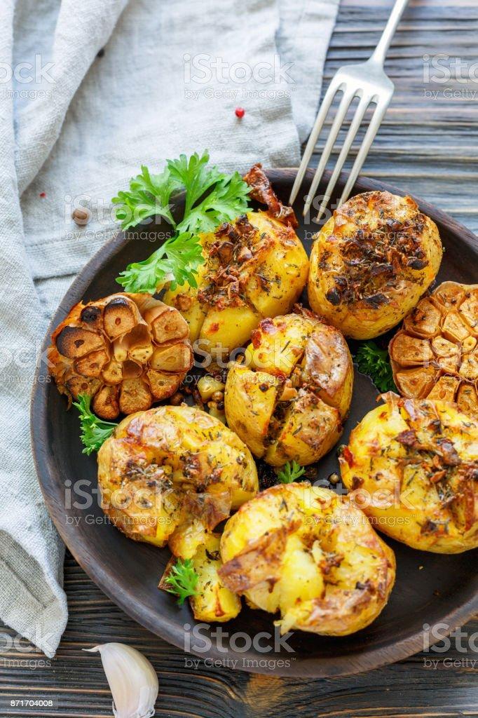 Batatas assadas com alho, tomilho e salsa verde. - foto de acervo