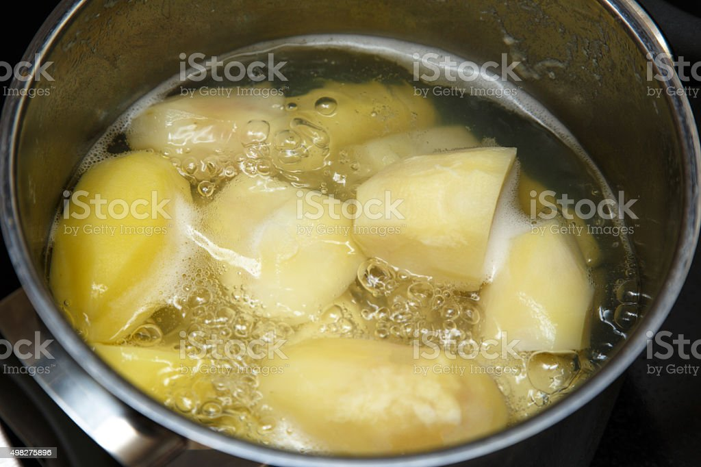 Potatoes boiling in saucepan stock photo