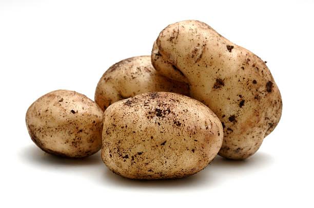 potatoes covered in soil against white