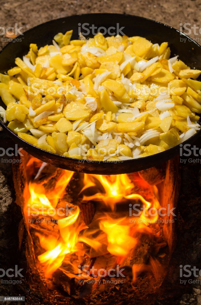 Potatoes fried in a frying pan in the open air stock photo