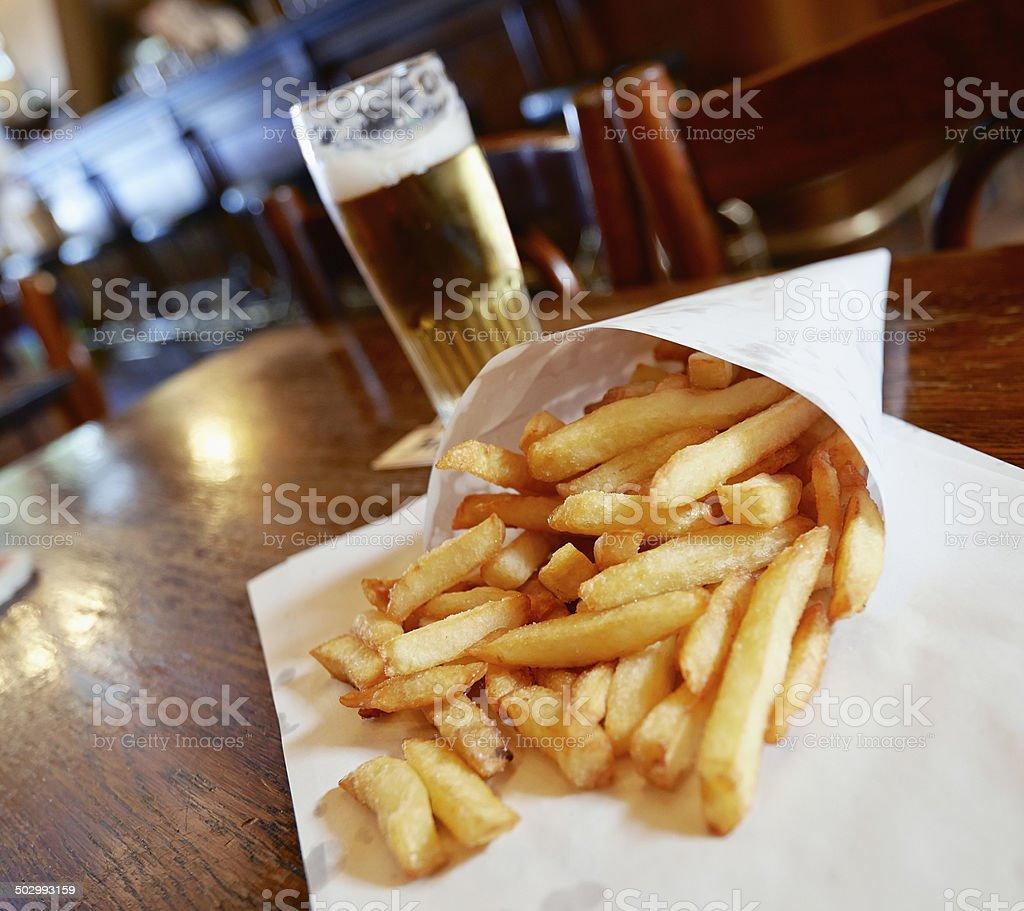 Potatoes fries in a little white paper bag stock photo