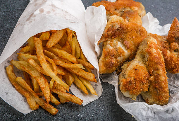 Potatoes fries in white paper bag and chicken wings stock photo