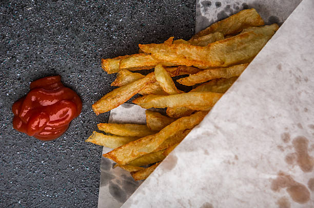 Potatoes fries in white paper bag on a black background stock photo