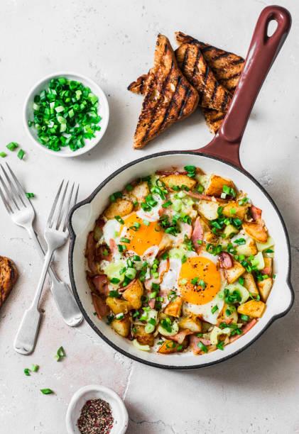 kartoffeln, schinken, eier frühstückshash in einer pfanne auf hellem hintergrund, top-aussicht. leckeres, nahrhaftes frühstück, snack - kartoffel frittata stock-fotos und bilder
