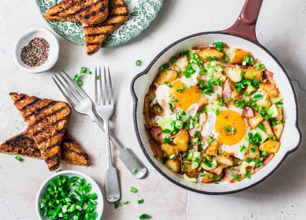 Kartoffeln, Schinken, Eier Frühstück Hasch in einer Pfanne auf einem hellen Hintergrund, Ansicht von oben. Köstliches, nahrhaftes Frühstück, Snack – Foto