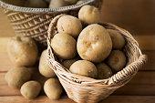 potatoes in a wicker basket on wood.
