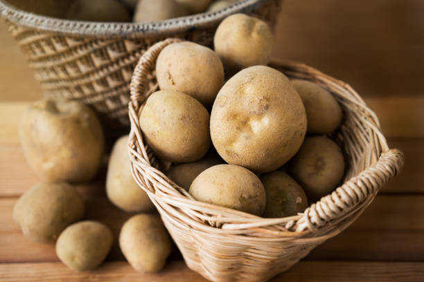 potatoes in basket. potatoes in a wicker basket on wood. raw potato stock pictures, royalty-free photos & images