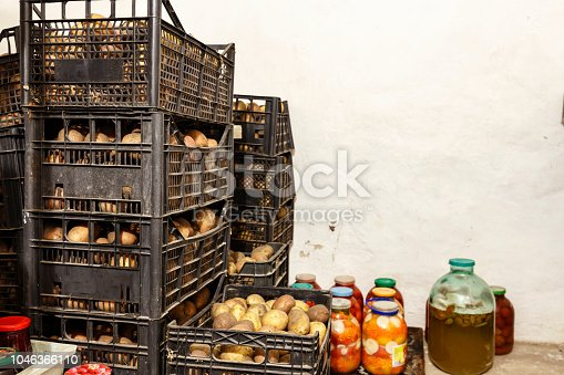 potatoes in boxes in the cellar. there are glass jars with conservation