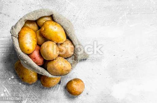 Potatoes in the sack. On white rustic background
