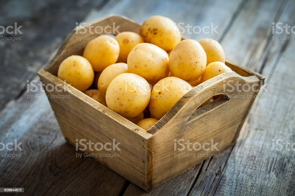 Potatoes in wooden box. stock photo