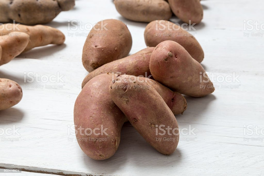 Potatoes on white wooden board Concept stock photo