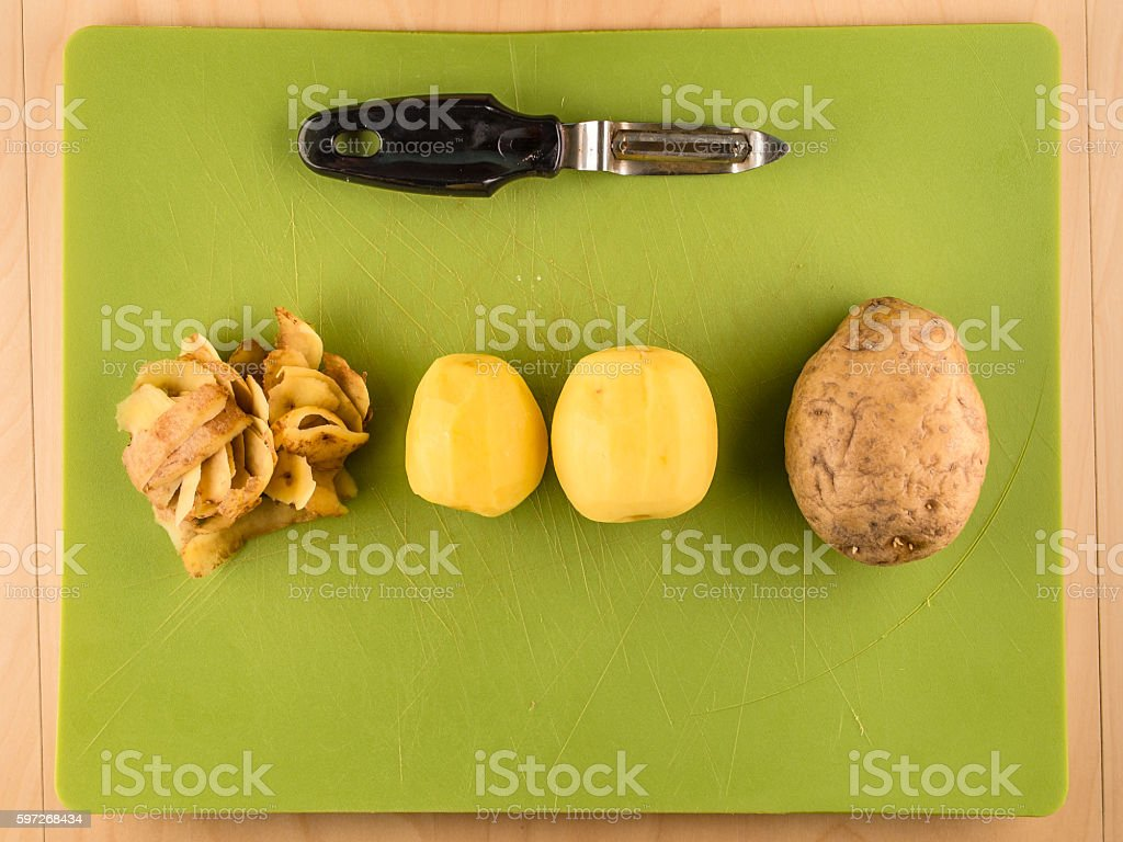 Potatoes, skins and peeler on green plastic board photo libre de droits