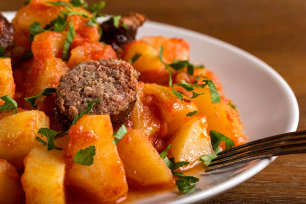 Potatoes stew with pork sausages on plate stock photo