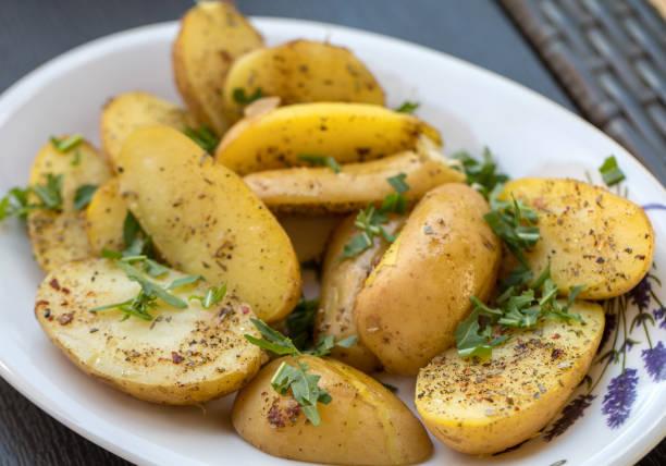 kartoffeln mit kräutern mit grüner petersilie bestreut - salzkartoffel stock-fotos und bilder