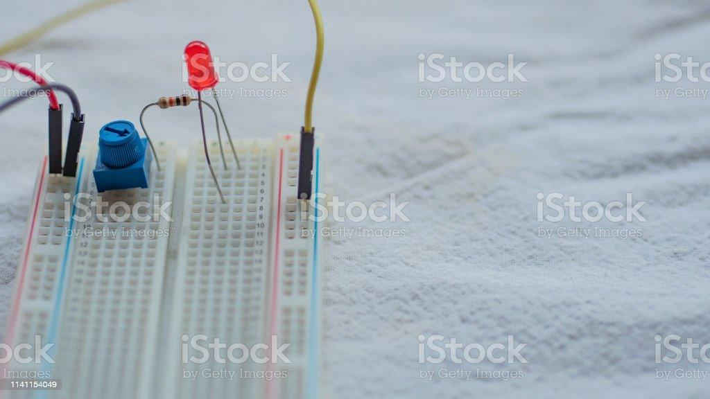 Potenciómetro, resistencias y LED rojo configurados en un tablero de pan - foto de stock