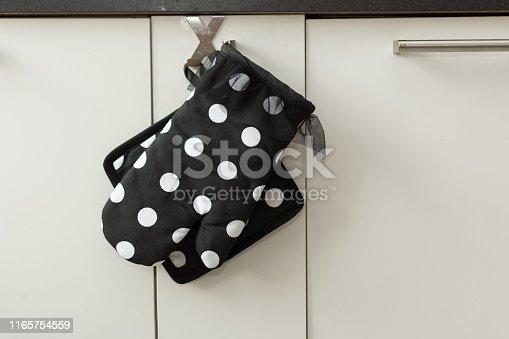 839034546 istock photo Potholder and an oven mitt in modern kitchen interior. 1165754559