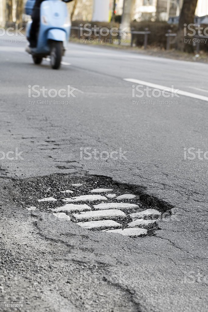 Pothole and approaching motorbike royalty-free stock photo