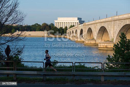 Washington DC, USA - June 25, 2016: A man jogs beside the George Washington Memorial Parkway and the Potomac River in Washington DC. Behind him is the Arlington Memorial Bridge and Lincoln Memorial.