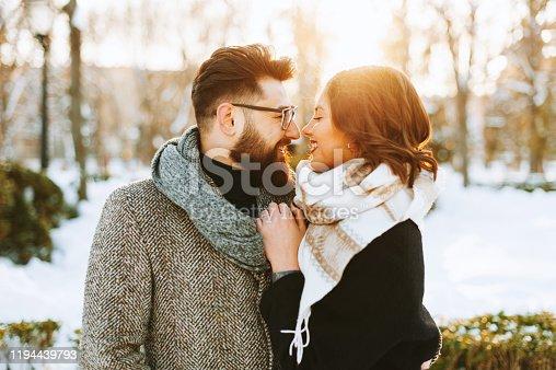 Potrait of a couple, having a winter walk, hugging on sunset lights