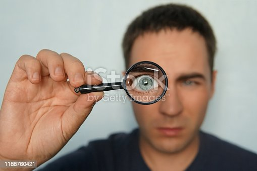 istock Potrait of a man holding magnifying glass and looking through it srewing up one eye. Funny view to magnified man's glass through magnifier. Man uses loupe to look intently to the some object. Macro. 1188760421