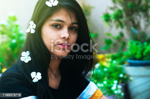 Indian teenager girl in outdoor with white flower in hair. beauty concept. shoot location Delhi.