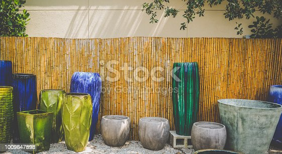 Bamboo fence and brightly colored pots for gardening. Lots of texture, color and copy space