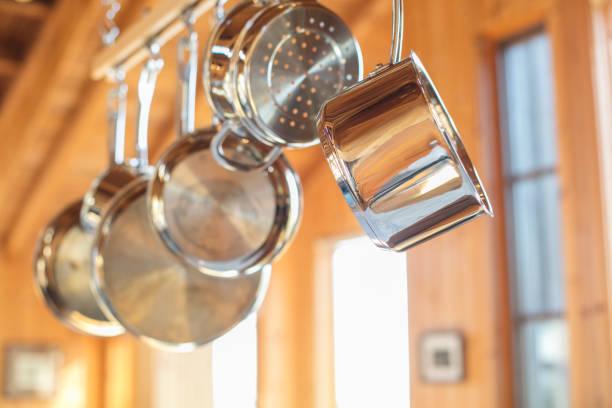 potten en pannen opknoping in keuken van houten rek: roestvrij staal - steelpan pan stockfoto's en -beelden