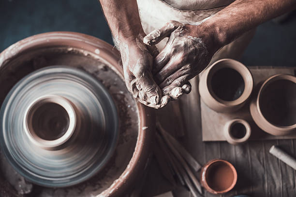 Potter at work. Top view of potter standing near pottery wheel and holding hands together ceramics stock pictures, royalty-free photos & images