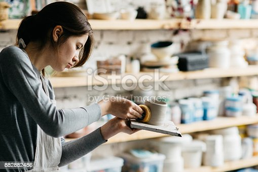istock Potter creating a shape of ceramic object 882882486